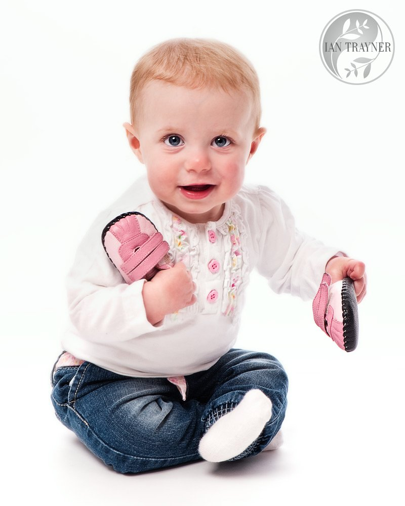 Seated baby looking at camera and playing with shoes. High key baby photography.