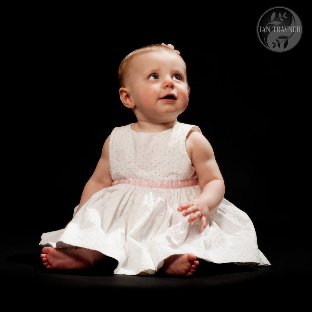 Cute baby girl photographed in the studio. Black background.