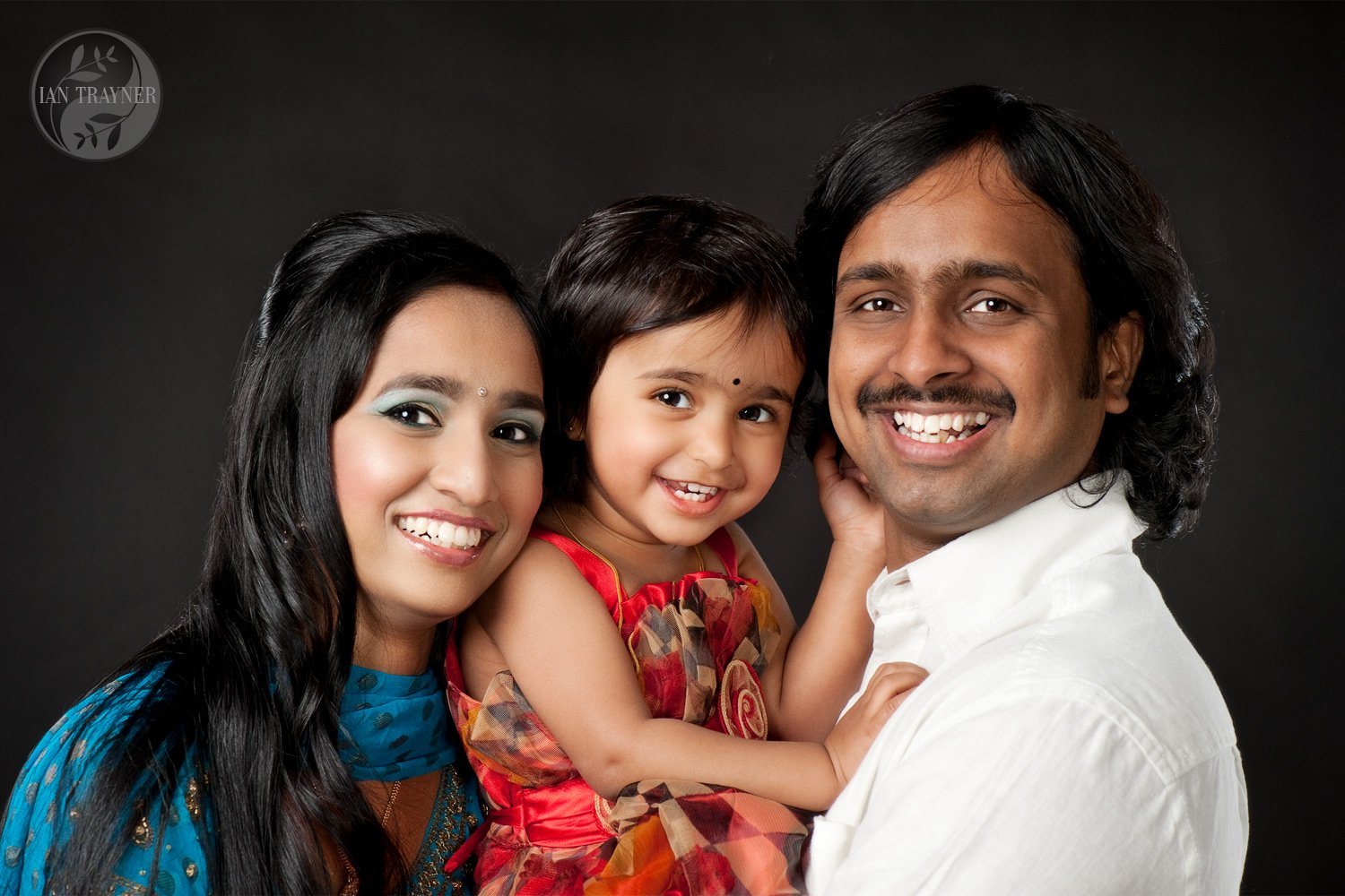 Happy asian family photographed in my studio. Parents and cute daugher.