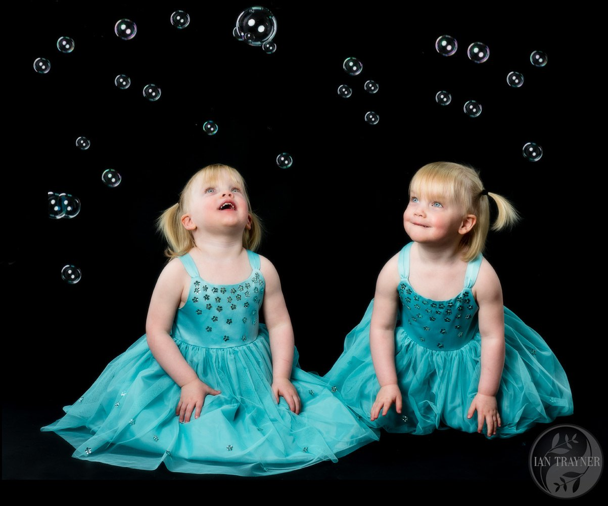 Twin sisters playing with bubbles. Family photo shoot. Bubble photo shoot.