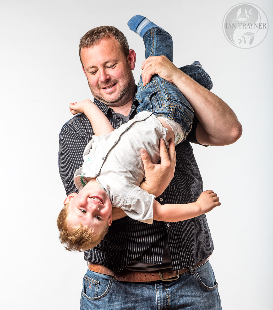 Dad holding his laughing son upside down. Happy family photography. High key family photo shoot.