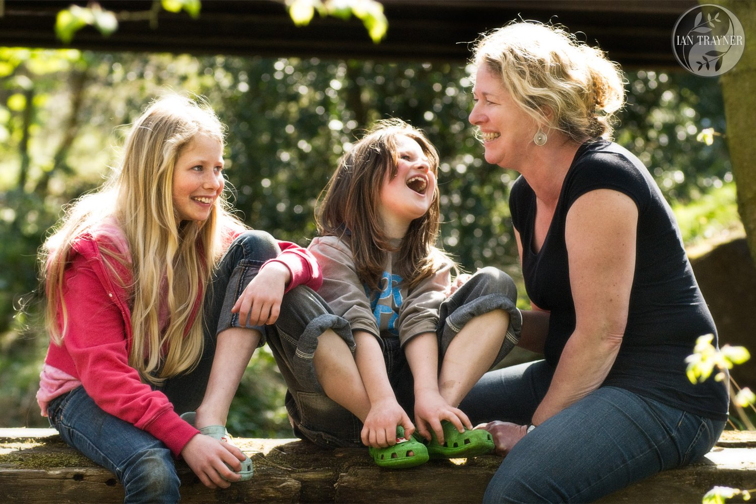 Happy family photography. Mother with two daughters laughing in the sunshine. Lifestyle family photo shoot on location.