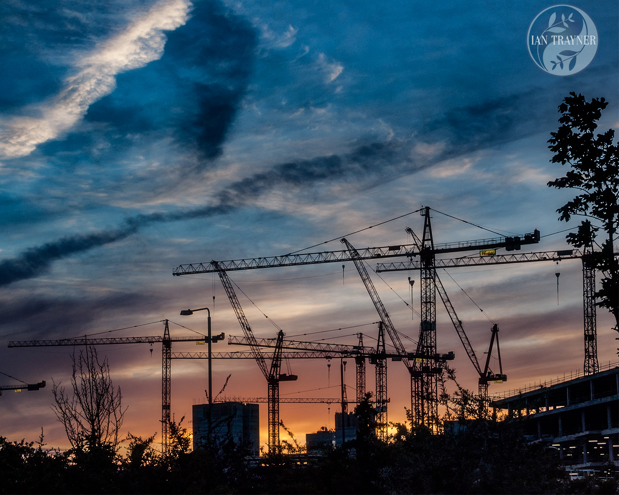 Dramatic sky at sunset. Cranes building the Westfield London shopping centre in Shepherd's Bush. Photo by Ian Trayner.
