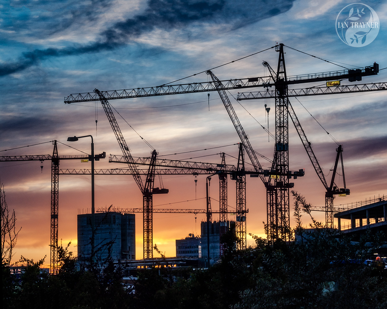 Cranes silhouetted against the sunset. Westfield London during construction. Photo taken by Ian Trayner in 2007.