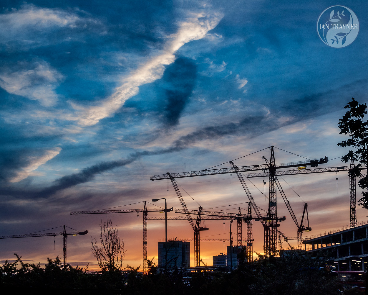 Stunning skyscape with sihouetted cranes. Construction of the Westield London shopping centre. Photo taken by Ian Trayner in 2007.