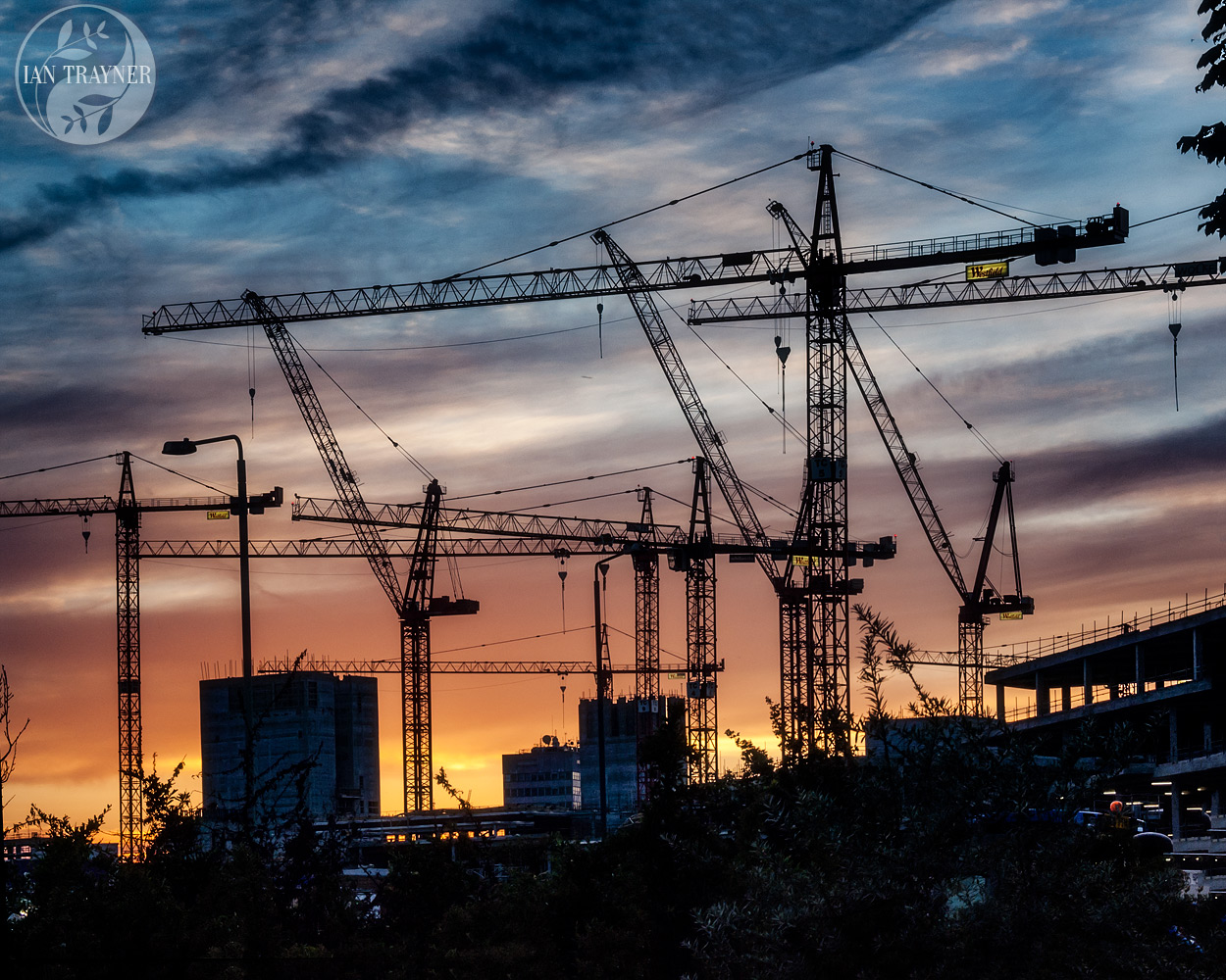 Westfield London during construction. Photo of dramatic sky and sunset, with cranes in silhouette. Photo by Ian Trayner, 2007.