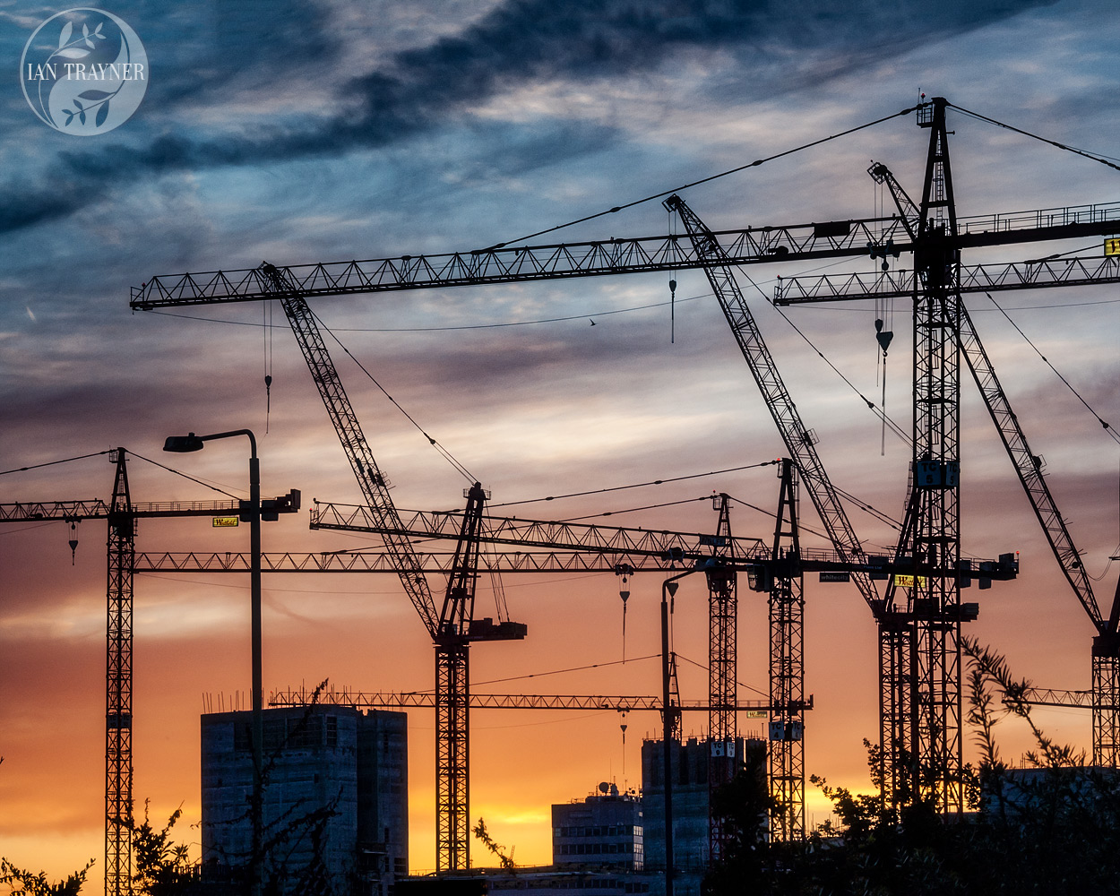 Cranes silhouetted against a stunning sunset sky looking towards Heathrow. Photo taken by Ian Trayner in 2007, during construction of the Westfield London shopping centre.