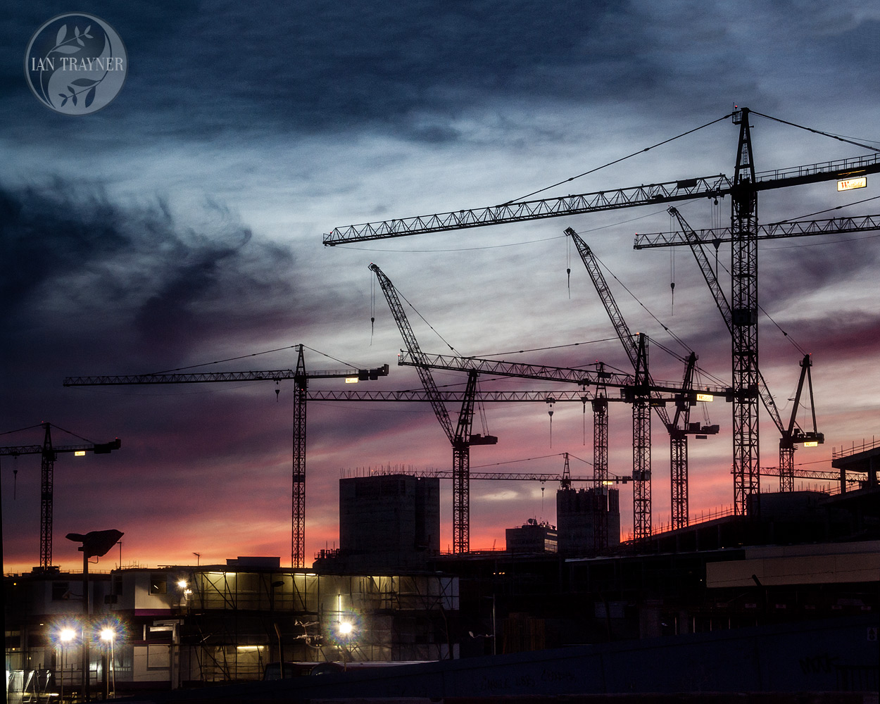 Dusk is falling. Cranes silhouetted against the sunset. Construction of Westfield London in 2007. Photo by Ian Trayner.