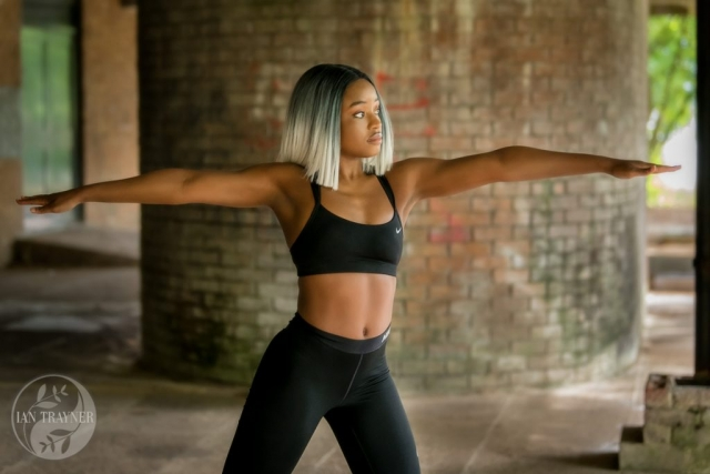 Fitness photo shoot - beautiful black fitness model Yollanda Musa photographed by Ian Trayner. She is doing some stretches.