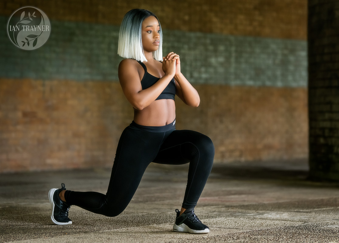 Fitness photo shoot. Beautiful black fitness model Yollanda Musa photographed by Ian Trayner using natural light. She is doing some lunges (leg exersizes).