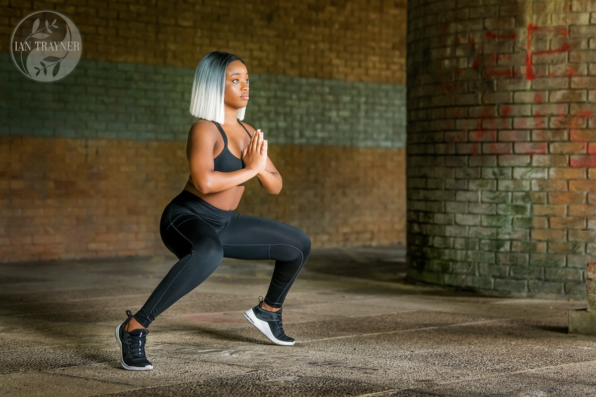 Fitness photo shoot. Beautiful black fitness model Yollanda Musa doing leg exersizes. You need really good balance for this as well as strong things. Wig by Precious Muir Collection. Photographer is Ian Trayner. Natural light only.