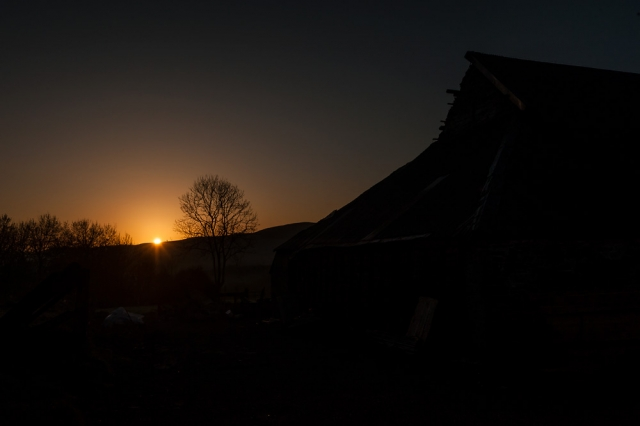 The Magic of Light. The sun rises in the Welsh hills. Barn silhouetted agains the morning sky.