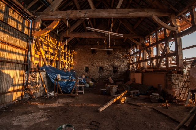 The yellow light of the early morning sun streams into the old barn.
