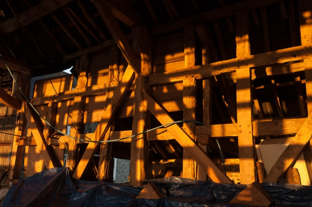 The warm light of the warming sunbeams glows yellow on the wooden beams