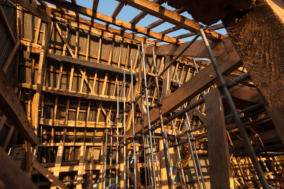 The sunlight reveals the renovation work that is waiting to be done on the old barn.